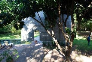 """""""La casa esta ubicada en un lote suburbano de 2.400 m2 (20m X 40m) a 20 Km. de Asunción, la vegetación es típica de la zona con árboles nativos de buen porte y una pequeña plantación de frutales al centro del terreno. El volumen principal se implanta en el centro en un claro del terreno con un formato rectangular en posición transversal este-oeste y el volumen que contiene a los locales de servicio y quincho al oeste sobre la medianera construido con la idea de un movimiento de suelo y con un techo jardín. La idea esencial se construye pensando en el comportamiento estructural de una viga simplemente apoyada con voladizos a los extremos como contrapeso de la posible deformación de una gran luz libre al centro. La casa se apoya sobre cuatro columnas en planta baja con una luz de 15 mts libre y dos voladizos laterales al extremo de 3.90 mts., la planta alta se cierra con dos placas apoyadas sobre las columnas y sobre estas se apoyan dos grandes vigas de 1.60 m en posición longitudinal que soportan y cuelgan las losas de techos, entrepisos, finalmente todos los estos elementos se ordenan en una suerte de síntesis formal en un solo movimiento en forma de rulo que definirán, un gran espacio abierto y transparente en planta libre sobre el nivel del terreno, un espacio intimo y cerrado al interior del giro y otro para instalaciones técnicas o doble techo como respuesta al clima"""""""