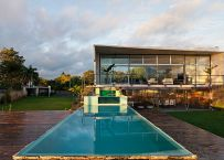 Swimming pool in the foreground and concrete volume in the backg